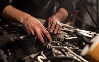 Car mechanic working under the hood of a vehicle